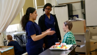 CNA students give each other advice during their clinical exercises.