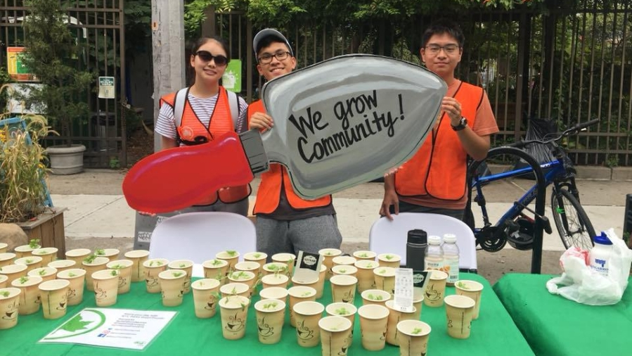 """Garden Train volunteers hold up a posterboard shaped like a garden spade with the words, """"We grow community"""" written on it"""
