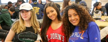 Three girls facing the camera inside of a school cafeteria wearing college shirts.