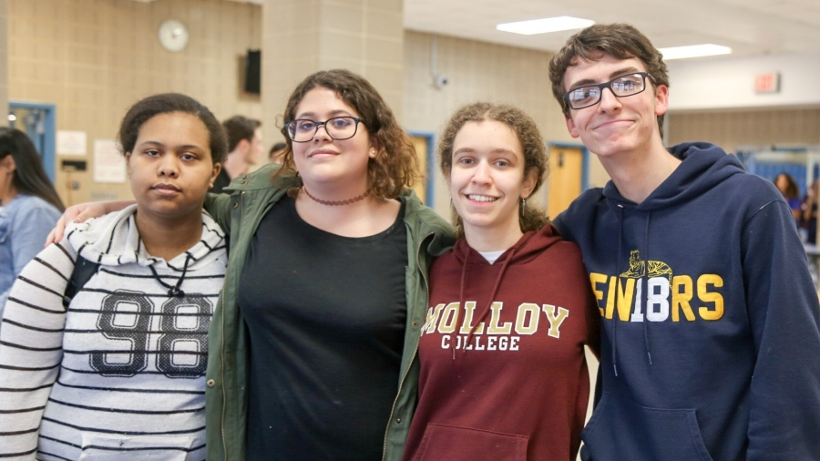 Four high school seniors looking into camera. One student, second from right, is wearing a Molloy College sweatshirt.