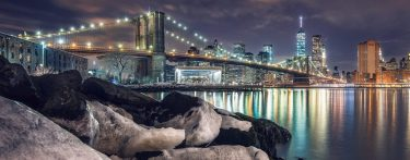 Photo of the Brooklyn Bridge during December evening. In the foreground are snow covered rocks.