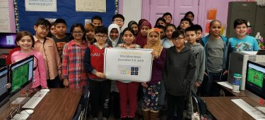 "Classroom's worth of students posing for photo while holding a sign that says, ""Computer Science Education Week, December 3–9, 2018"""